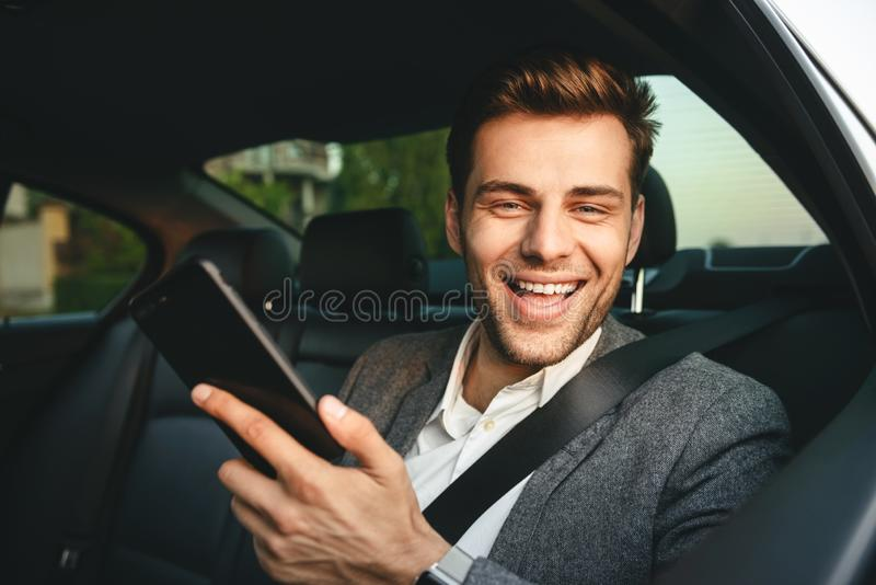 Image of young director man in suit holding smartphone and smiling, while back sitting in business class car with safety belt. Image of young director man in royalty free stock photo