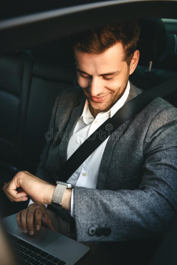 Image of young director man in suit working on laptop and looking at wrist watch, while back sitting in business class car with s. Image of young director man in royalty free stock images
