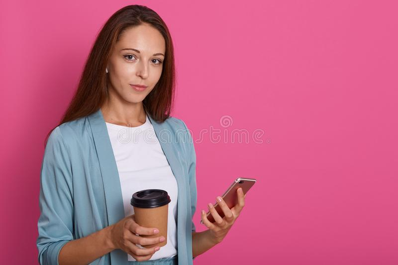 Image of young european woman with staraight hair holding mobile phone and takeaway coffee in paper cup, model posing isolated stock photography