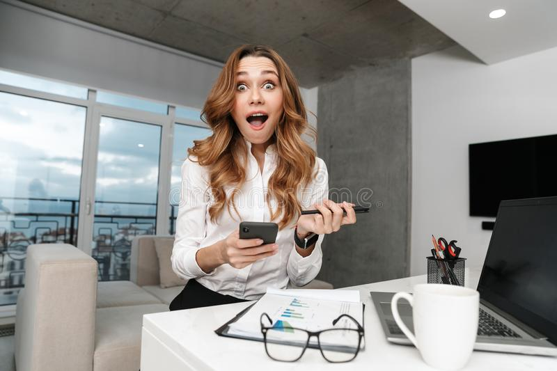 Business woman dressed in formal clothes shirt indoors using mobile phone royalty free stock photo