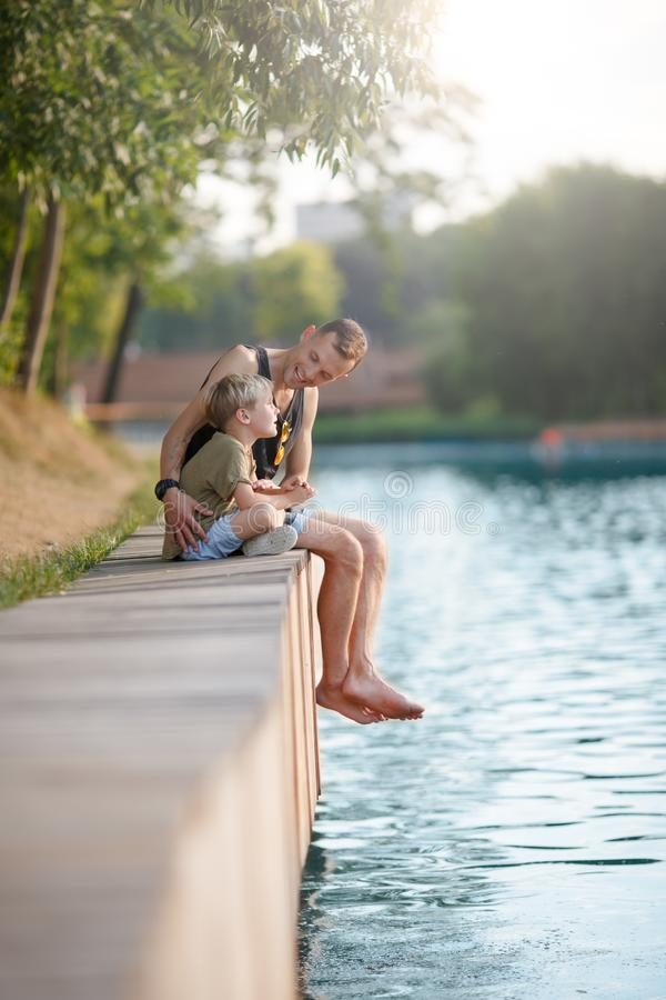Image of young father and boy sitting on wooden bank by river royalty free stock photo