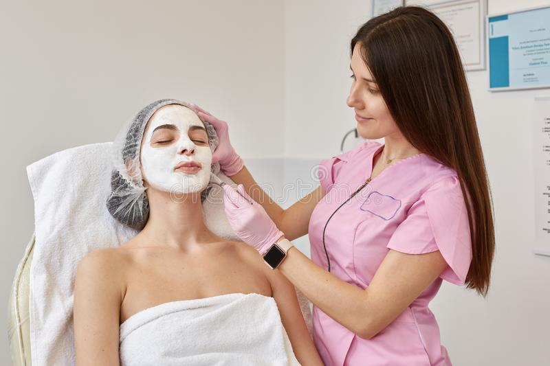 Image of young female with face peeling mask, spa beauty treatment. Woman getting facial care by beautician at spa salon. stock photo