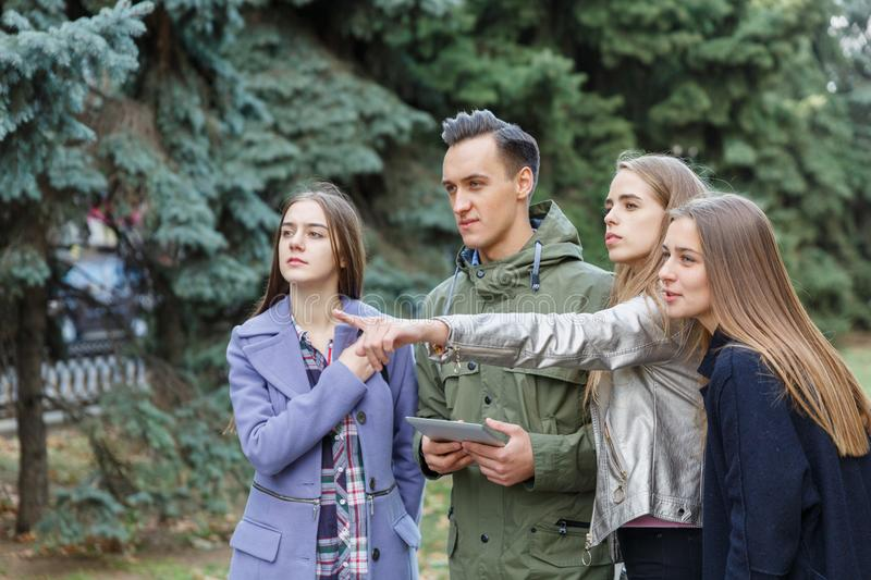 Image of young friends outdoors with a computer in hands of a young man. stock image