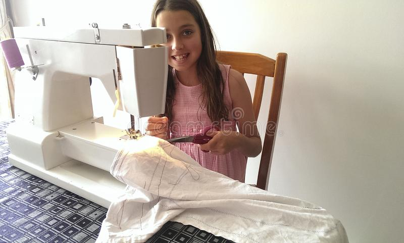 Young girl peering out from a sewing machine that she is learning to use stock image