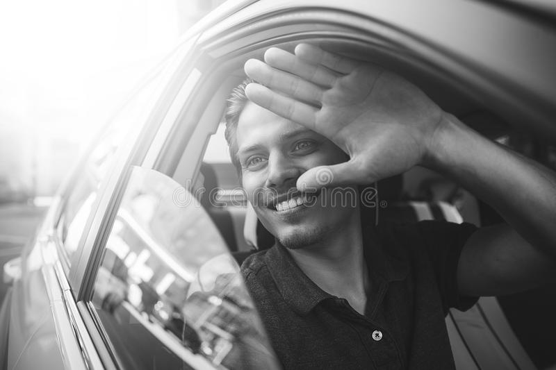 Say hello. Close up side portrait of happy caucasian man driving car. royalty free stock images