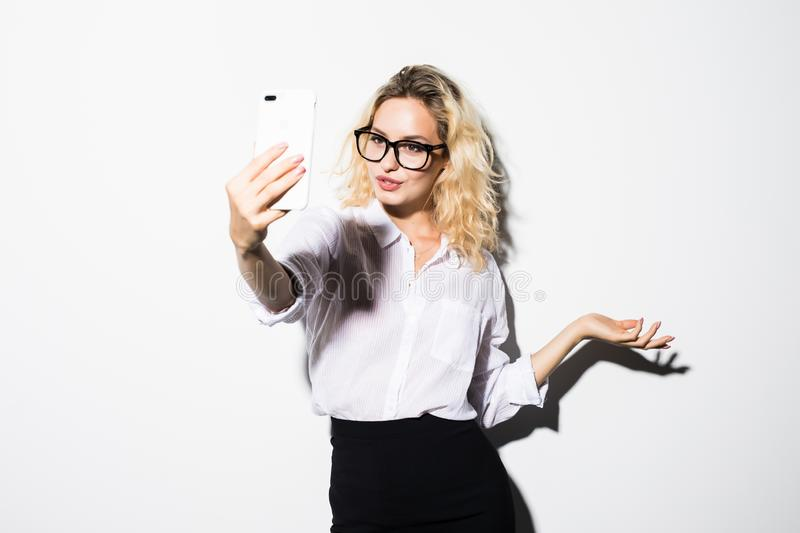Happy business woman looking aside talking video call by phone waving to friends isolated over white wall backgound . royalty free stock images