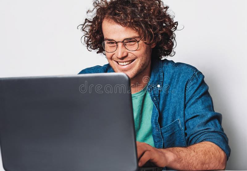 Image of young happy businessman with curly hair working on his laptop in office. Cheerful smiling student man sitting at his desk royalty free stock images