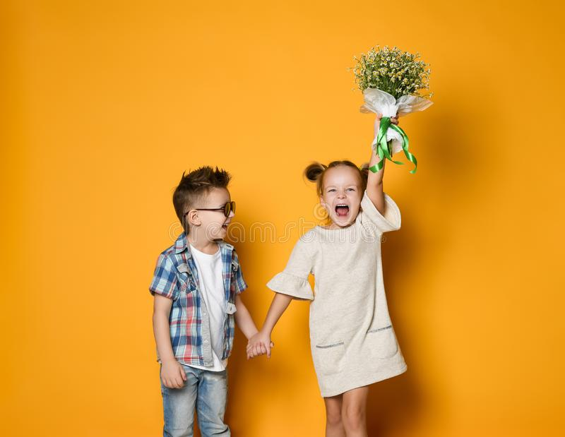 Image of young happy caucasian boy gives a flowers to his girlfriend isolated over yellow background. stock image