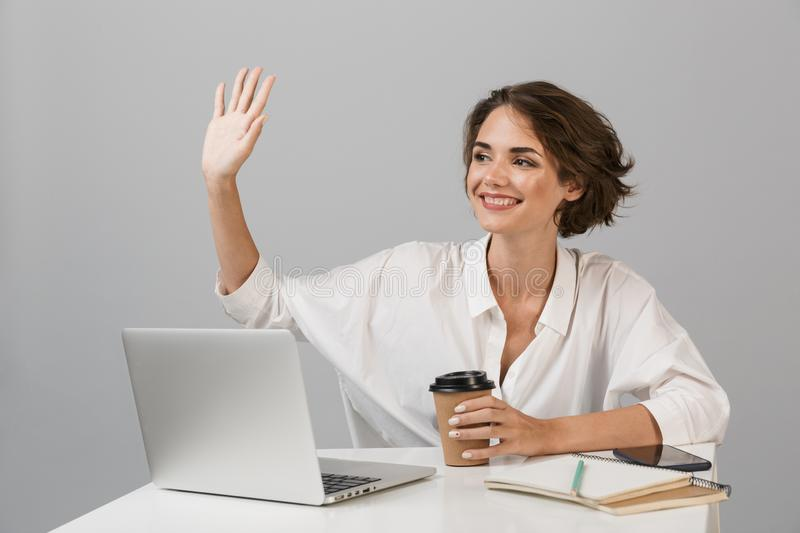 Happy cheerful business woman posing isolated over grey wall background sitting at the table using laptop stock photography