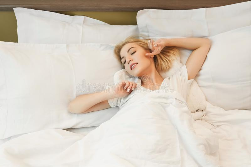 Image of young lady lying in bed in hotel room stock photo