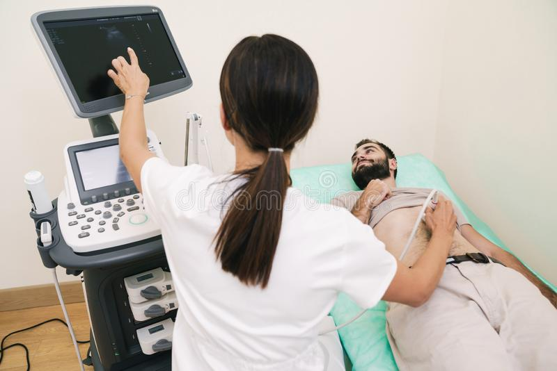 Image of young man getting abdominal ultrasound scan by female doctor royalty free stock image