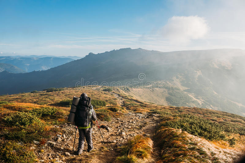 Image of young man mountaineer standing atop rock stock photos