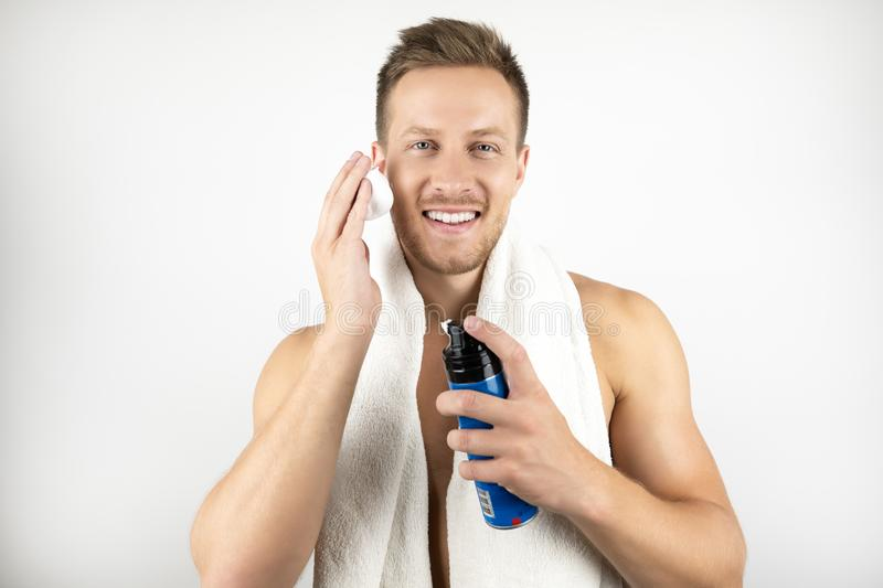 Image of young man with white towel on his shoulders holding applying shaving foam on his face during his morning stock photo