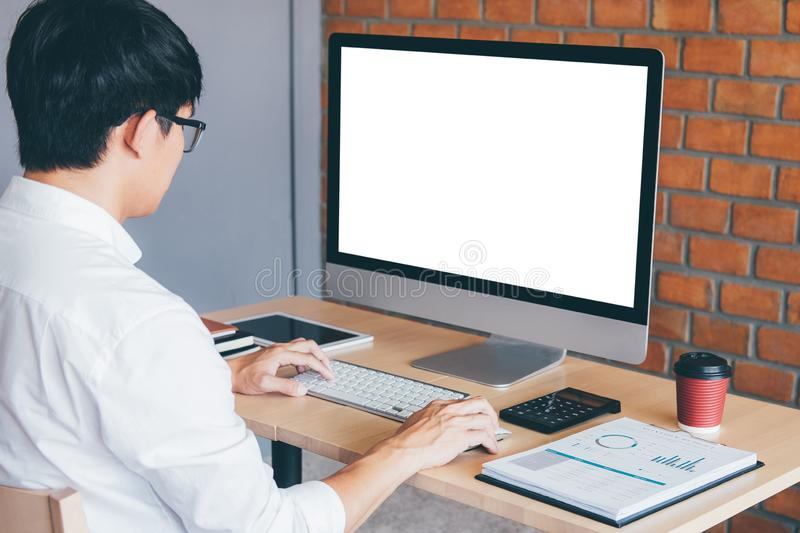 Image of Young man working in front of the computer laptop looking at screen with a clean white screen and blank space for text stock photo