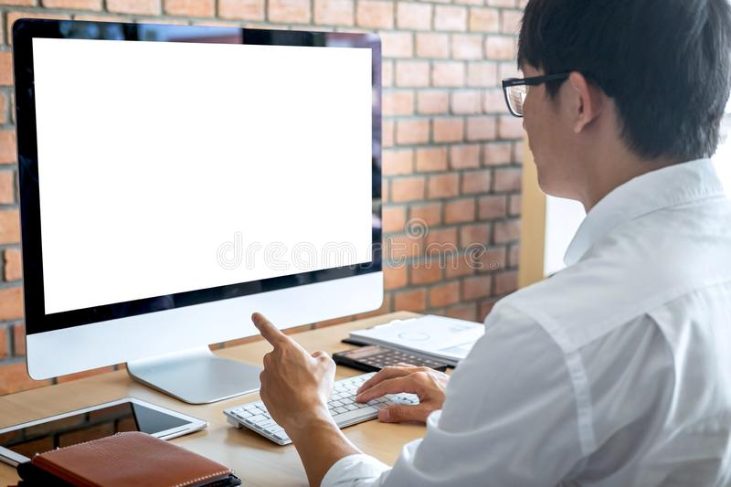 Image of Young man working in front of the computer laptop looking at screen with a clean white screen and blank space for text royalty free stock image