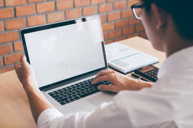 Image of Young man working in front of the laptop looking at screen with a clean white screen and blank space for text and hand stock images