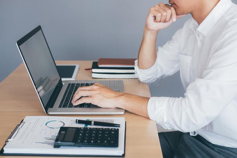 Image of Young man working in front of the laptop looking at screen with a clean white screen and blank space for text and hand stock photo