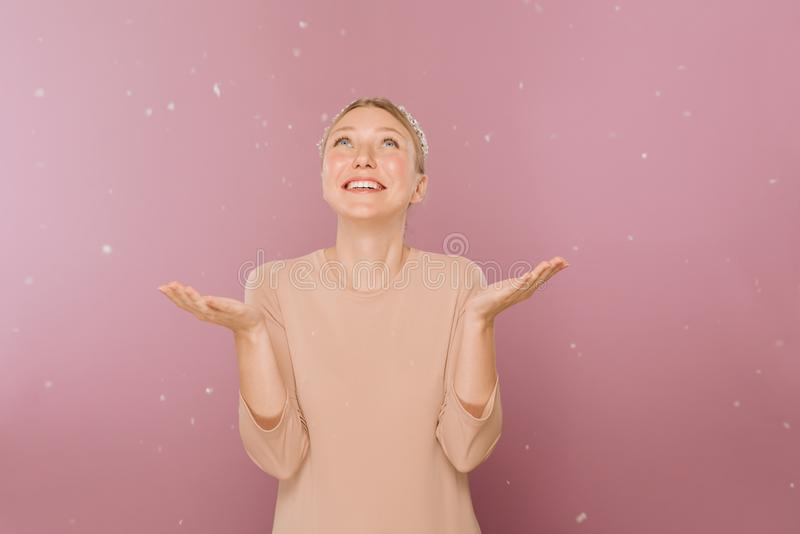 Image of young pretty woman posing isolated over pink background. She smiles and looks up, her hands catching crystal stock image
