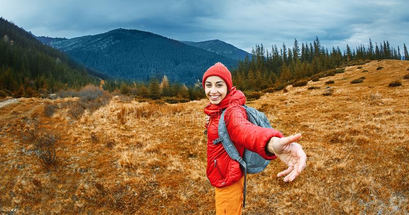 Image of a young smiling woman hiker with small backpack standing on a mountain slope. stock photography