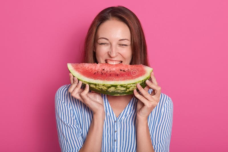 Image of young woman biting big slice of sweet watermelon while smiling and looking at camera, posing  over rose stock photography