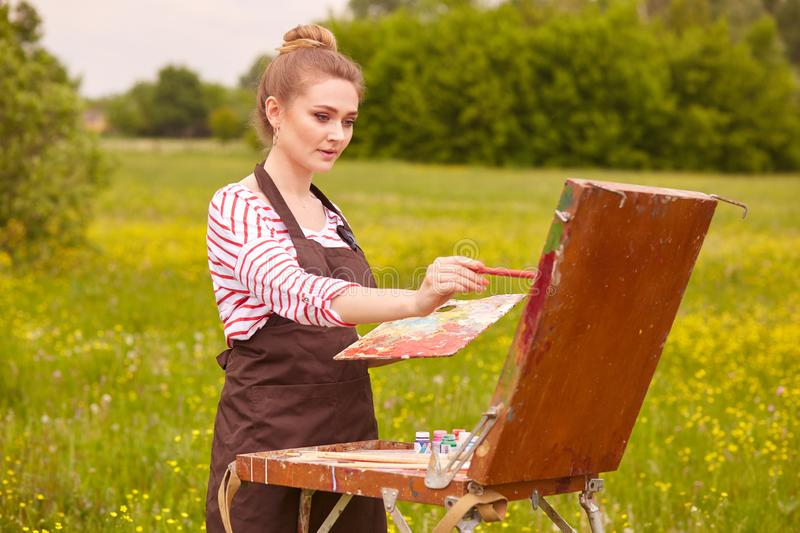 Image of young woman drawing picture, using sketchbook for drawing in nature, painter girl stands with brush and palette of royalty free stock photography