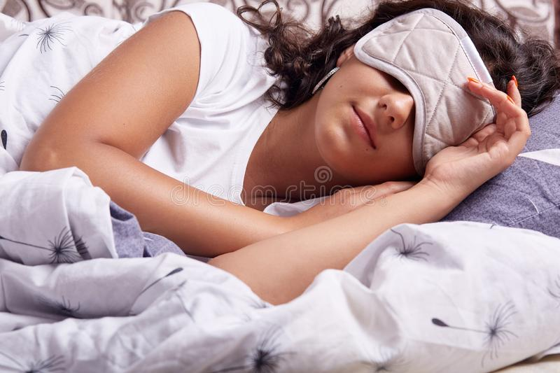 Image of young woman sleeping with eye mask, lying under cosy blanket in comfortable bed at home, brunette lady with wavy hair, stock photo