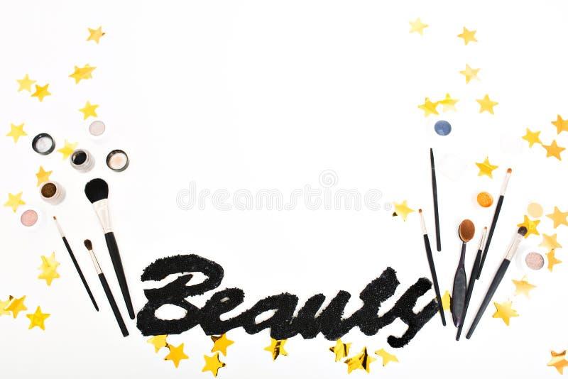 Imagem à moda do material da composição em torno das estrelas douradas dos ouropéis acima no fundo branco Beleza preta da inscriç fotos de stock