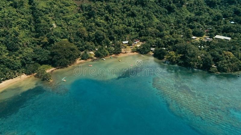 Imagem aérea do zangão de uma vila de South Pacific em uma ilha remota com um recife de corais bonito e uma selva tropical luxúri imagem de stock royalty free