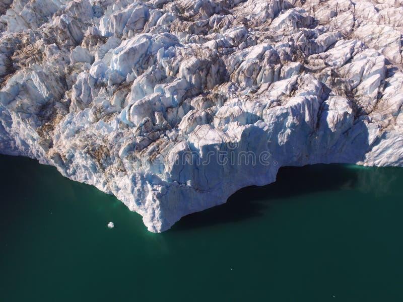 Imagem aérea do zangão do gelo que projeta-se do término de uma geleira em Gronelândia do nordeste em águas do oceano em um fiord fotografia de stock