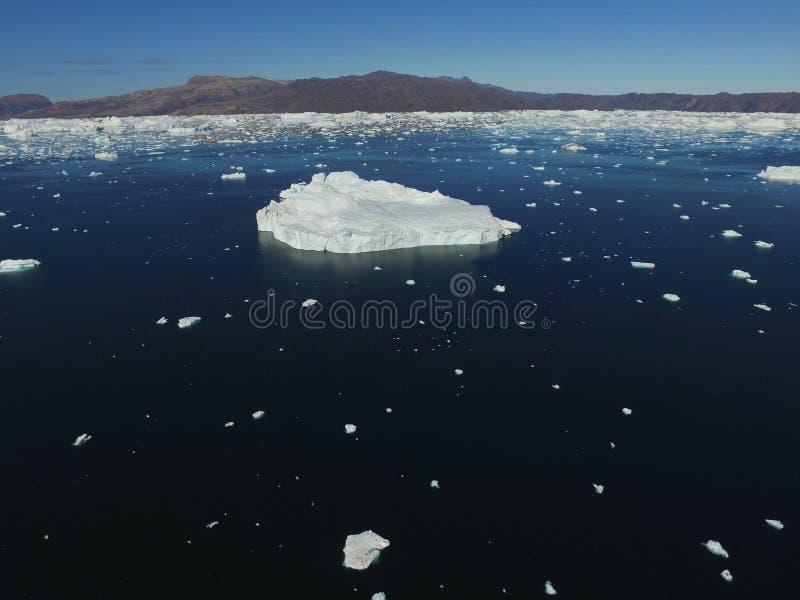 Imagem aérea do zangão oblíquo da baixa altura de um grande iceberg cercado por muitos iceberg menores perto de Upernavik, Gronel fotografia de stock royalty free