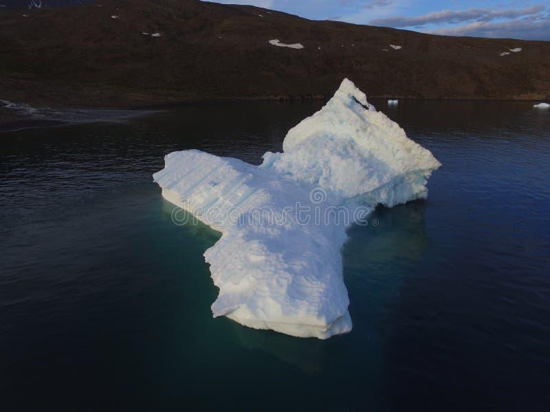 Imagem aérea do zangão oblíquo da baixa altura de um iceberg aterrado perto de uma ilha em Gronelândia ocidental foto de stock