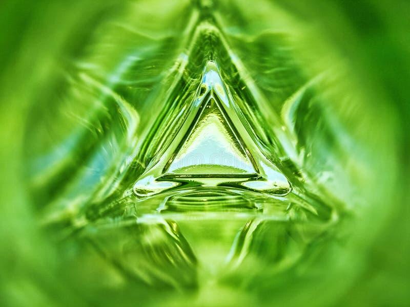 Imagem abstrata do interior de um fundo da cor verde de esmeralda da garrafa de vidro do triângulo foto de stock royalty free