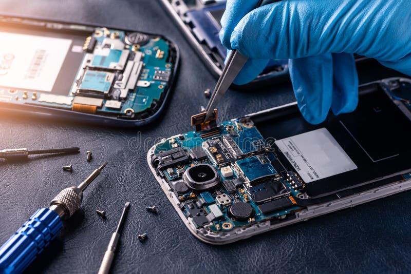 A imagem abstrata do técnico que monta dentro do smartphone pela chave de fenda no laboratório imagens de stock