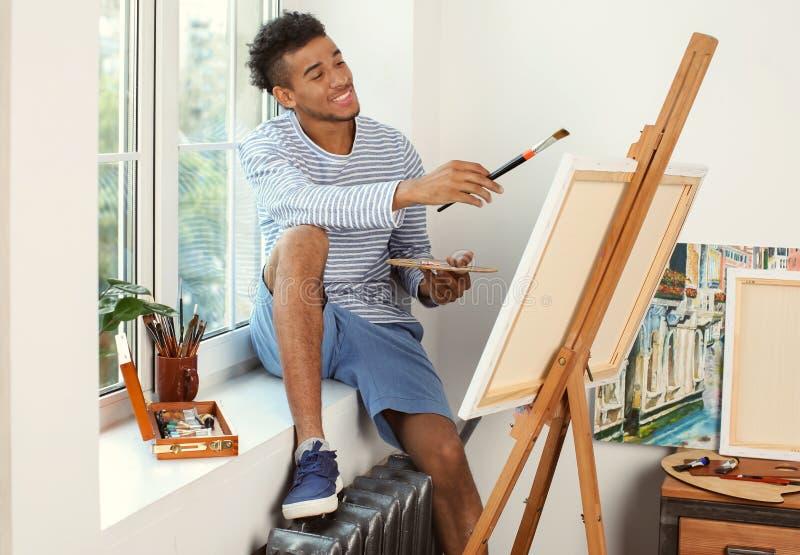 Imagem afro-americano nova da pintura do artista em casa fotografia de stock