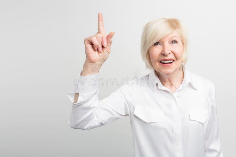 Imagem agradável da mulher adulta que está na parede branca e que aponta acima Uma ideia brilhante veio até sua mente Agora ela imagens de stock
