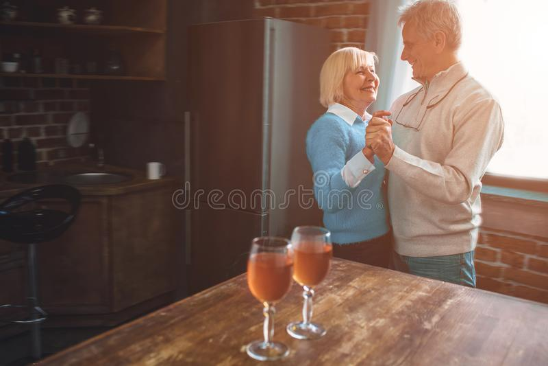 Imagem agradável e morna do ouple velho que dança junto no kitch imagem de stock