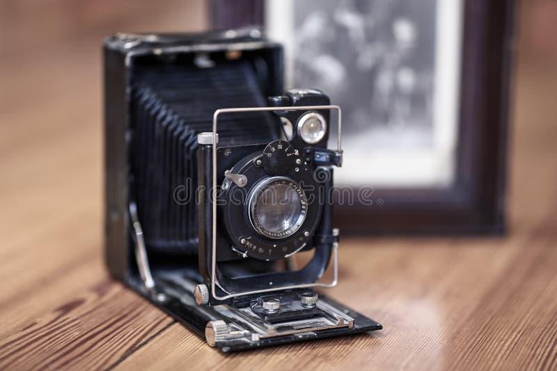 Imagem ascendente próxima da câmera empoeirada do vintage velho com imagem velha no fundo borrado, foco seletivo fotografia de stock