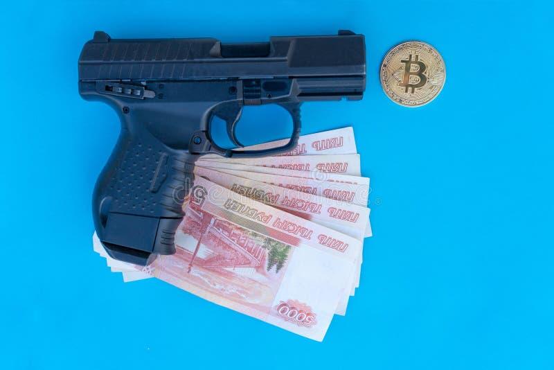 Imagem ascendente próxima da pistola, das moedas de Bitcoin e dos rublos do moneyon um fundo azul imagens de stock royalty free