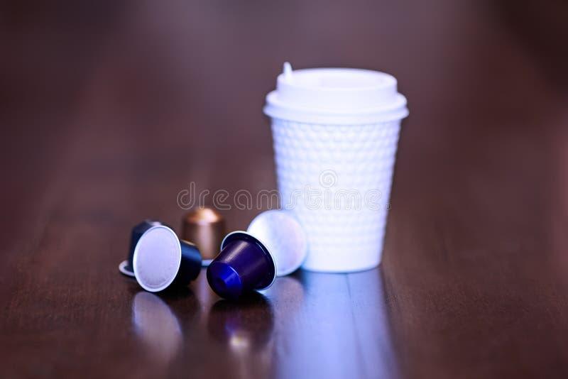 Imagem ascendente pr?xima do copo pl?stico branco do coffe com alguns cartuchos substitu?veis coloridos com caf? imagens de stock royalty free