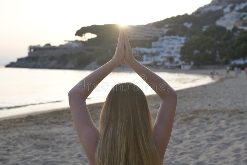 Imagem backlighting bonita de uma menina em uma posição da ioga de volta à câmera imagens de stock royalty free