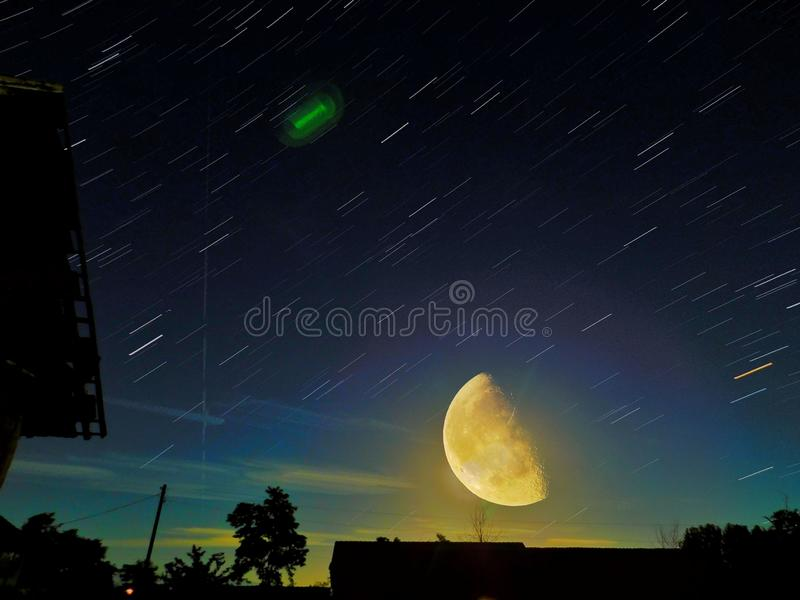 Imagem bonita da fuga da estrela com o SuperMoon na frase, com árvores, e telhado de construção abandonado foto de stock