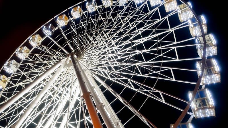 Imagem bonita da roda de ferris no stret da cidade iluminado com os bulbos brancos com céu noturno no fundo foto de stock royalty free