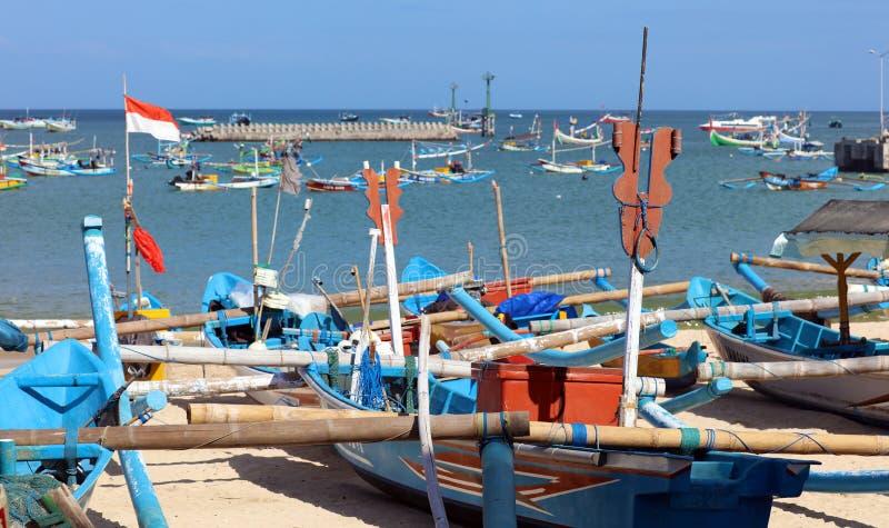 Imagem bonita de barcos de pesca na baía de Jimbaran em Bali Indonésia, praia, oceano, barcos de pesca e aeroporto na foto imagens de stock