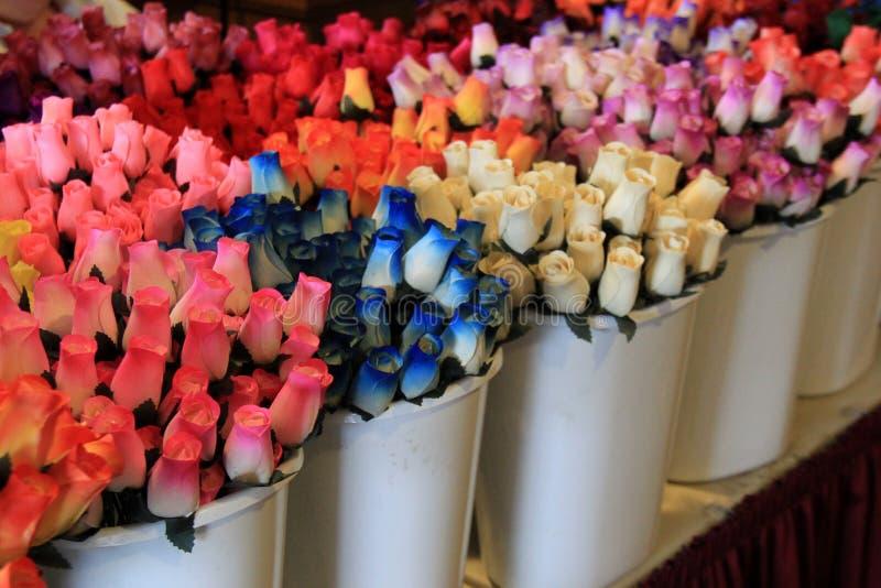 Imagem bonita de rosas de madeira tingidas na variedade de cores, colocada nos recipientes brancos na tabela fotografia de stock