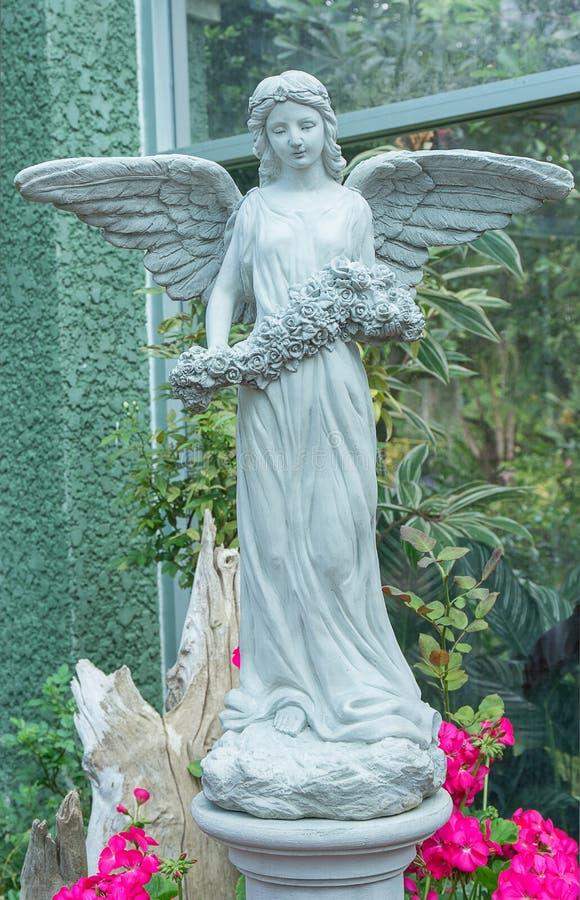 Imagem bonita de uma escultura do anjo que guarda o ramalhete das flores foto de stock royalty free