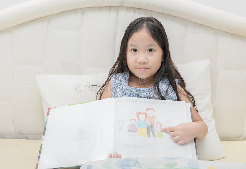 Imagem bonito da família da imagem da mostra da menina em seu livro do esboço fotografia de stock royalty free