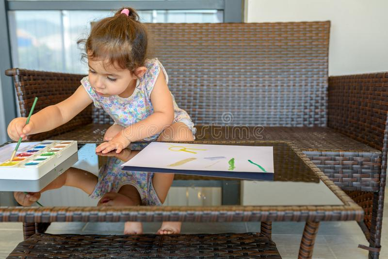 Imagem bonito da pintura da menina no fundo interior home Menino e meninas que sentam-se na mesa surfando e no olhar no mar azul foto de stock