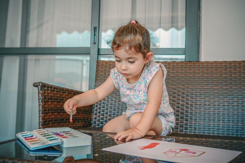 Imagem bonito da pintura da menina no fundo interior home Menino e meninas que sentam-se na mesa surfando e no olhar no mar azul fotografia de stock royalty free