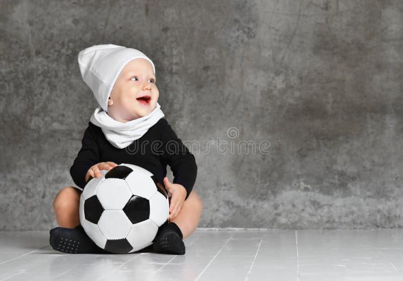 Imagem bonito do bebê que guarda uma bola de futebol imagens de stock royalty free