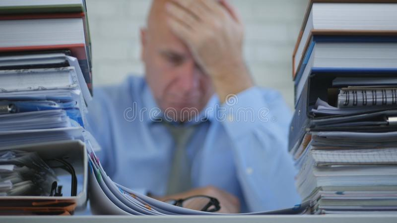 Imagem borrada com empresário Suffering uma dor de cabeça grande no escritório de contabilidade fotografia de stock royalty free